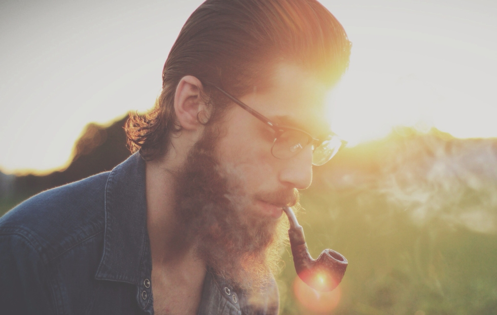 bearded man with pipe in summer sun