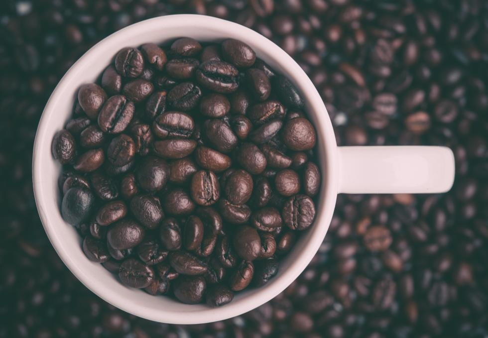 cup of coffee beans sitting in a pile of coffee beans